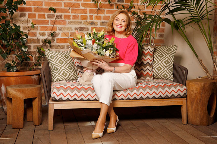 Mary Kennedy sitting on sofa holding a bouquet of flowers